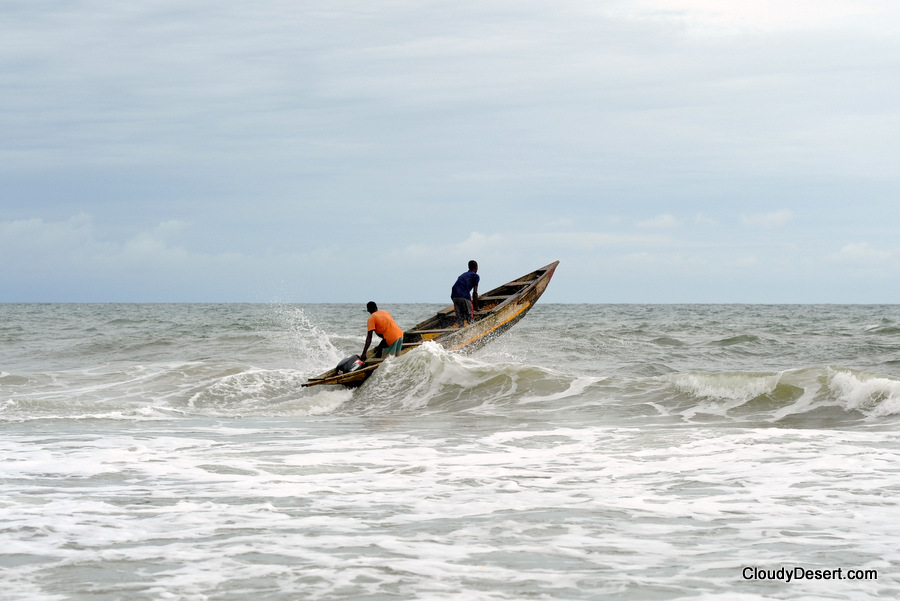 Fishermen launching boat from beach